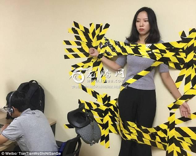 A female worker was taped to the wall in her office as a web user posted on Weibo today