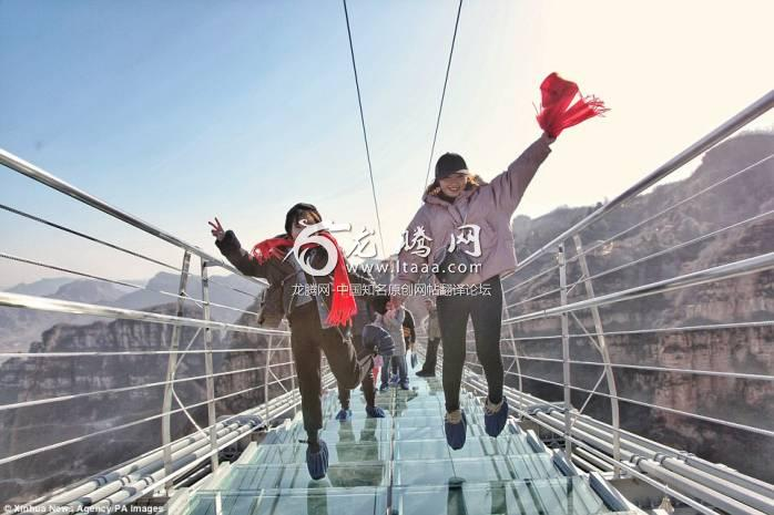 Daredevils: Tourists jump on the transparent suspension bridge  which has been designed to sway 755 feet above the ground