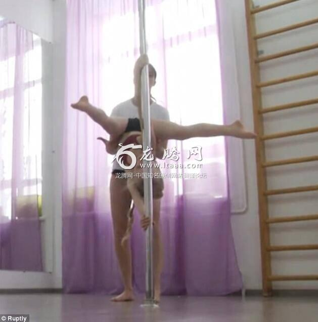 The girl performs moves like that of an acrobat under the guidance of her teacher